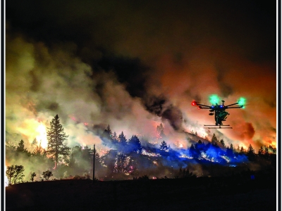 UAS flying at night with fire in the background